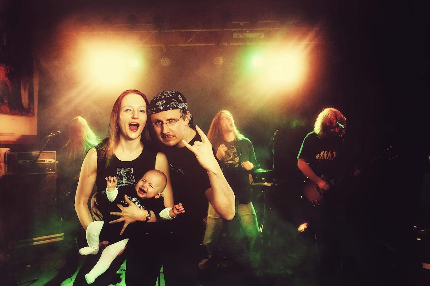 Eine junge Familie ist mit ihrem Saeugling auf einem Rock-Konzert.