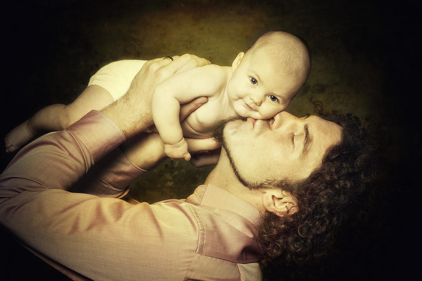 Ein Vater hält sein Baby über den Kopf