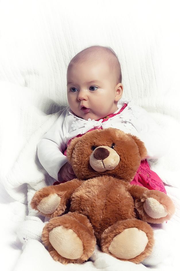 Baby sitzend mit Teddy im Arm