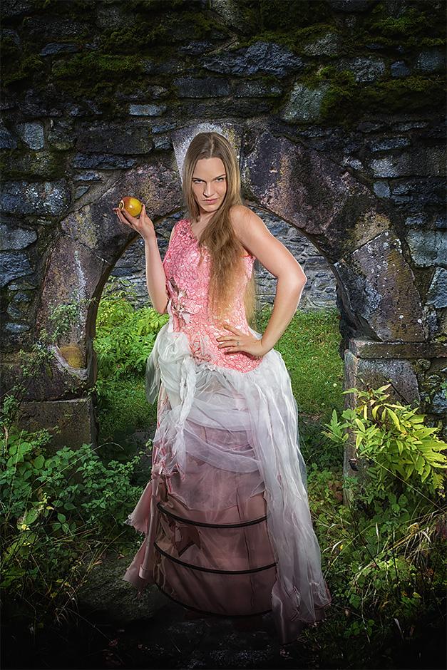 Die Versuchung. Eine Frau in romantischem Kleid bietet einen Apfel an. Kleid von Darkdirndl Historic Couture