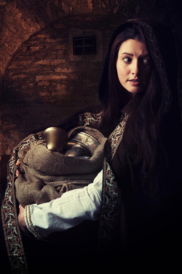Eine junge Frau im mittelalterlicher Gewandung trägt einen Sack mit Silber