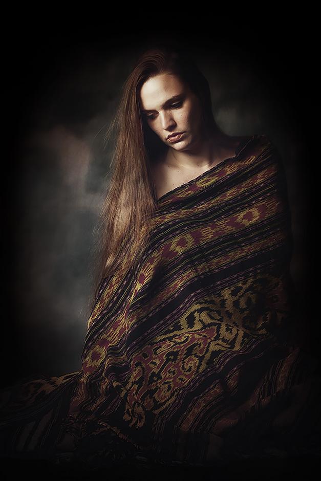 Eine Frau sitzt in eine Decke gehuellt