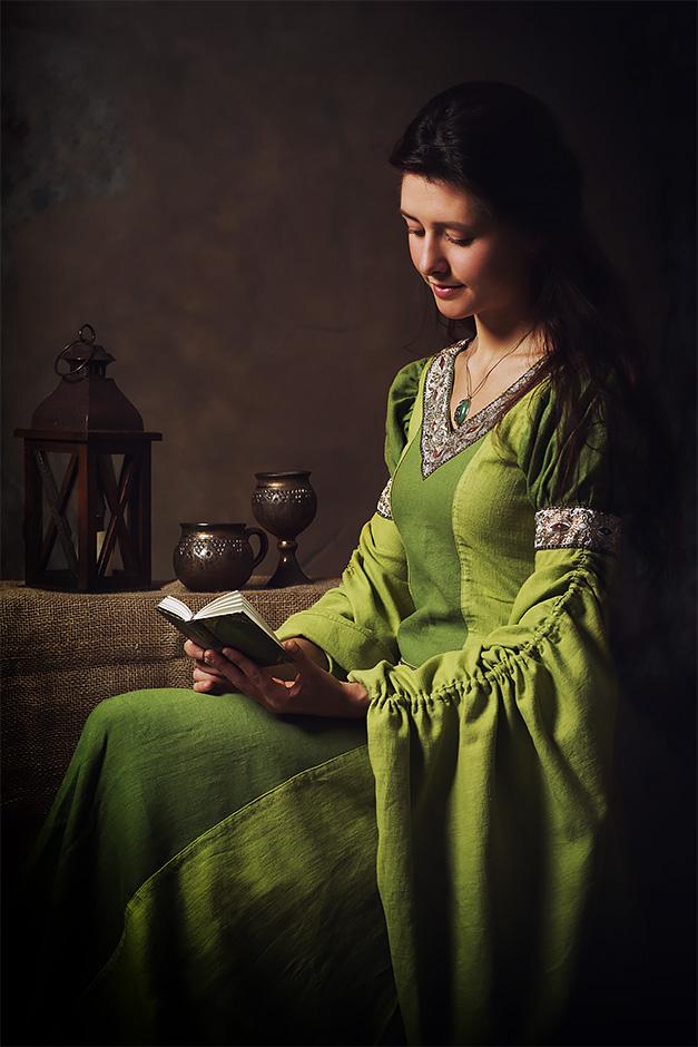 Eine Frau in mittelalterlichem gruenen Kleid liest ein Buch