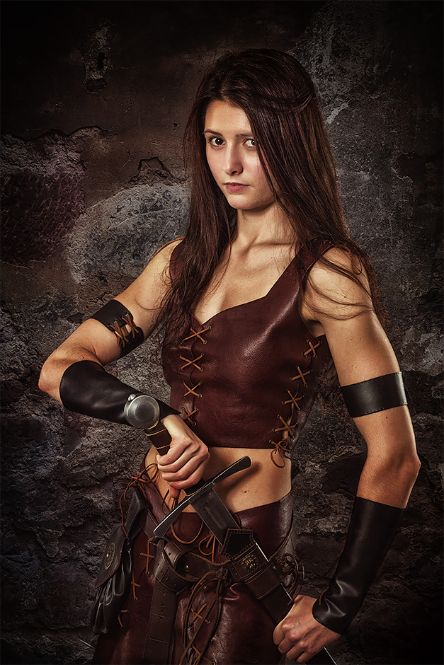 Dunkelhaarige schlanke Frau in Lederruestung mit Schwert