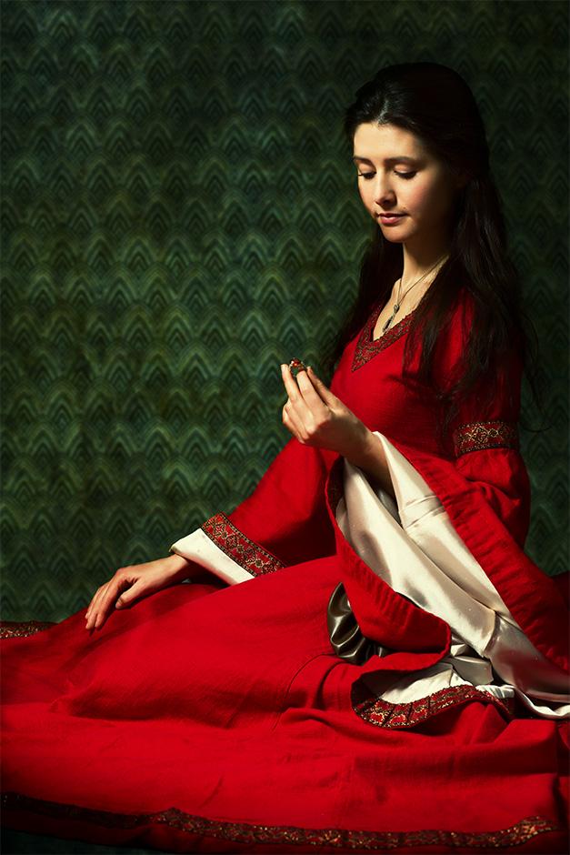 Eine Frau in rotem Kleid kniet auf dem Boden und betrachtet einen Ring