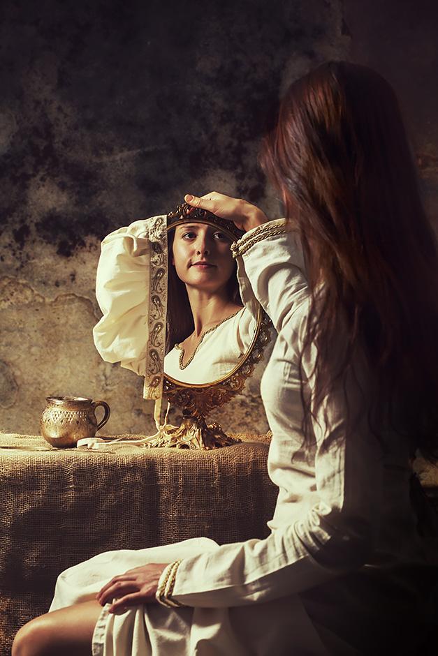 Eine Frau mit hellem Unterkleid sitzt vor einem alten Spiegel