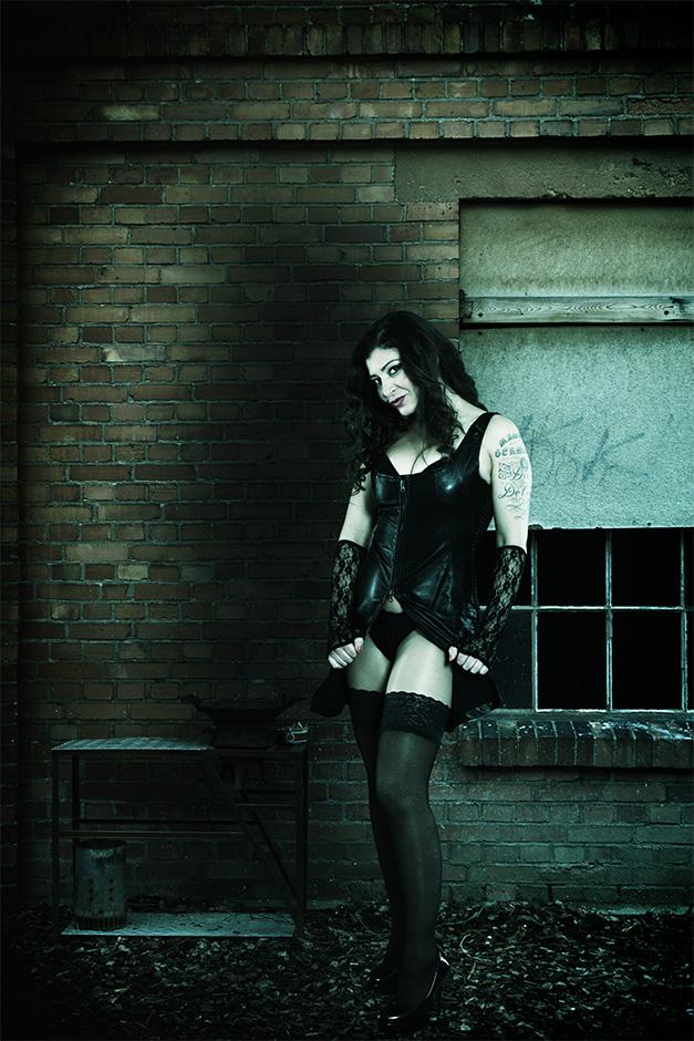 Eine dunkelhaarige Frau in Unterwäsche steht vor einer Hauswand