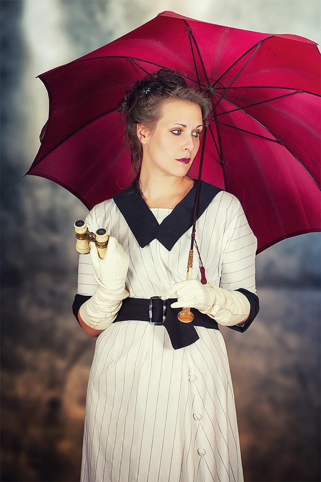 Frau mit Schirm und Opernglas in weissem Kleid. Kleid von Darkdirndl Historic Couture