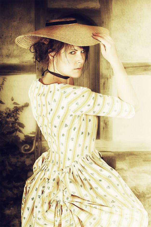 Frau in sommerlichem Kleid mit Strohhut. Kleid von Darkdirndl Historic Couture