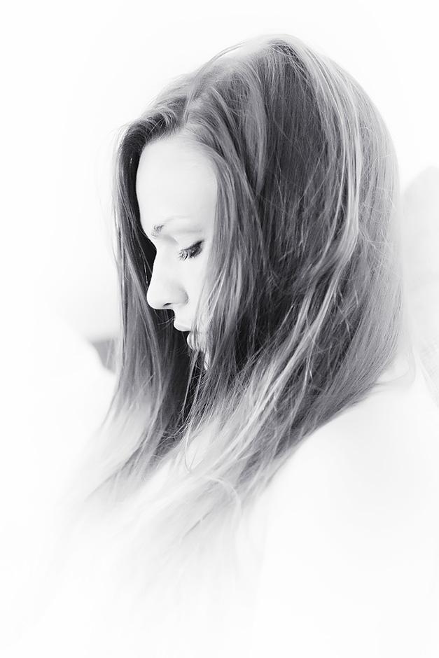 Schwarz-weiss Profil-Portrait einer Frau mit langen Haaren vor weissem Hintergrund