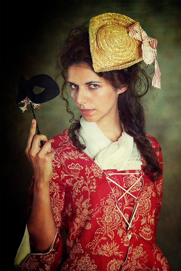 Frau mit Maske und Strohhut in rotem Kleid. Kleid von Darkdirndl Historic Couture