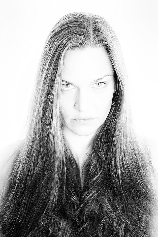Schwarz-weiss Portrait einer Frau mit langen Haaren vor weissem Hintergrund