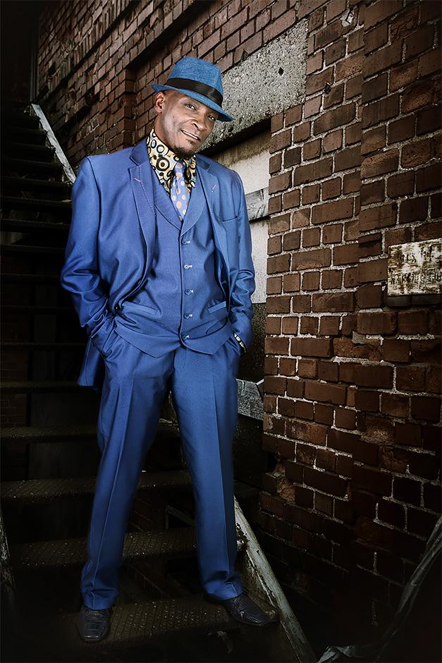 Keith Sanders - The Gypsys - steht auf einer Treppe an einem Backsteingebaeude