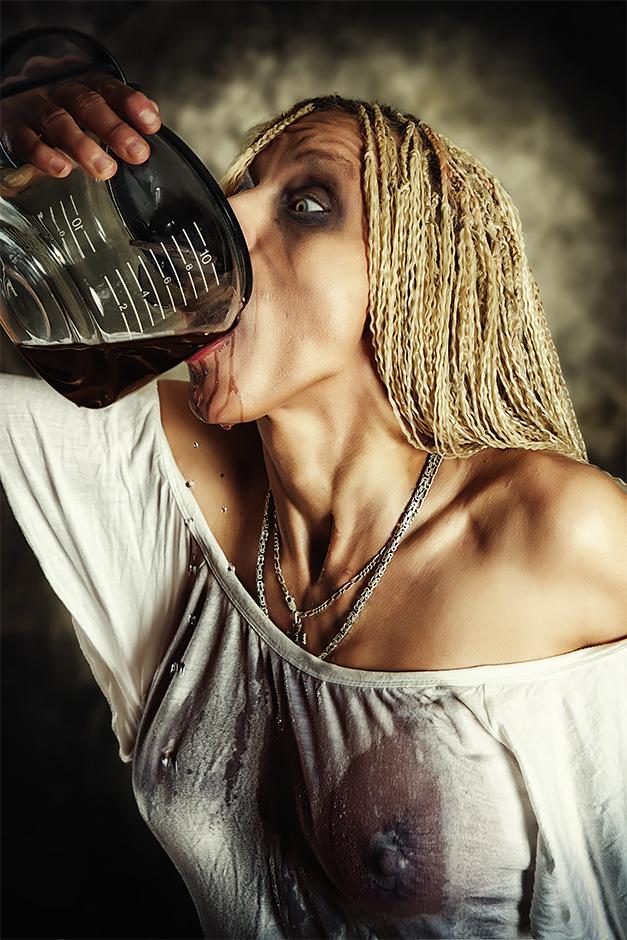 Frau im Nachthemd mit Augenringen trinkt gierig Kaffee direkt aus der Kanne