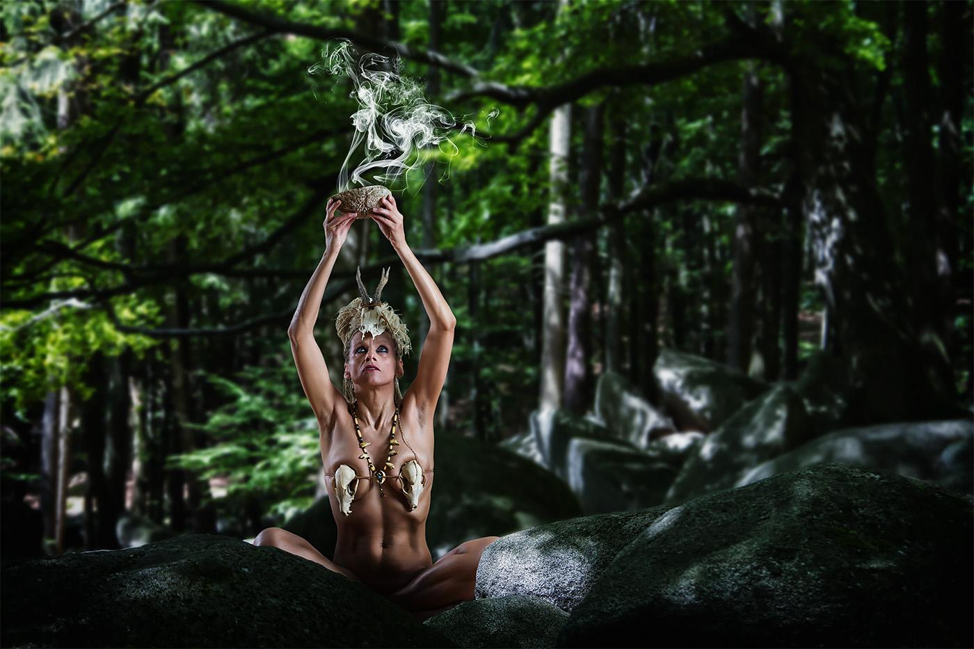 Eine Schamanin haelt im Wald eine Raeucherschale ueber den Kopf - Model Petra Wimmer