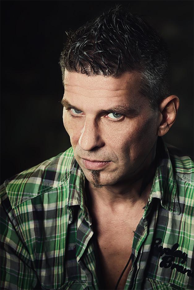 Portrait eines Mannes im gruenen Holzfaellerhemd