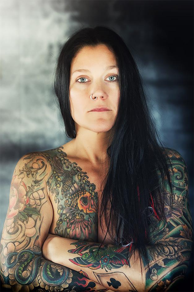 Frontal-Portrait einer taetowierten Frau mit dunklen Haaren