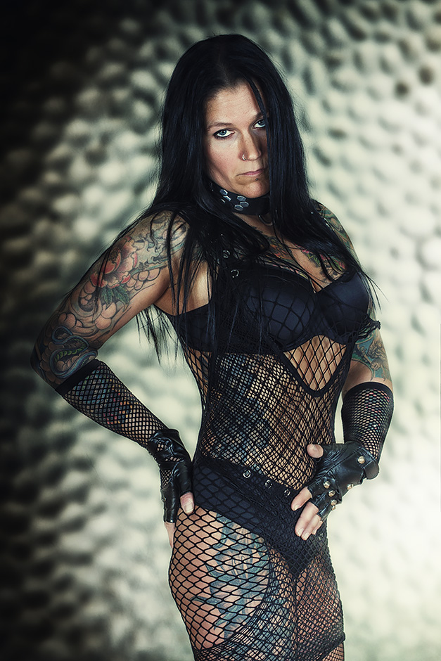 Tätowierte, dunkelhaarige Frau im Netz-Suit vor Metallwand