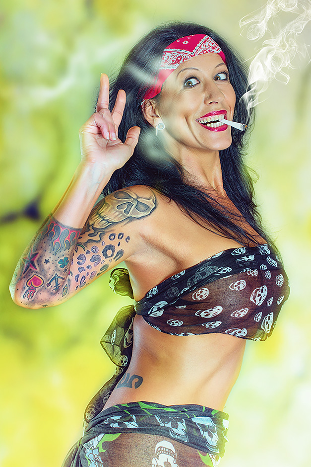 Dunkelhaarige Frau mit grossen Brüsten trägt ein Stirnband und hat einen Joint im Mund, bekleidet mit dünnen Tüchern mit Totenkopfmuster