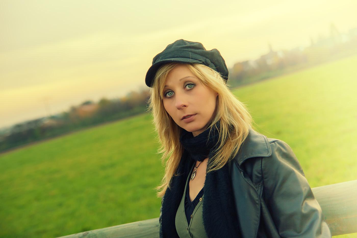 Blonde Frau mit Cap im Feld
