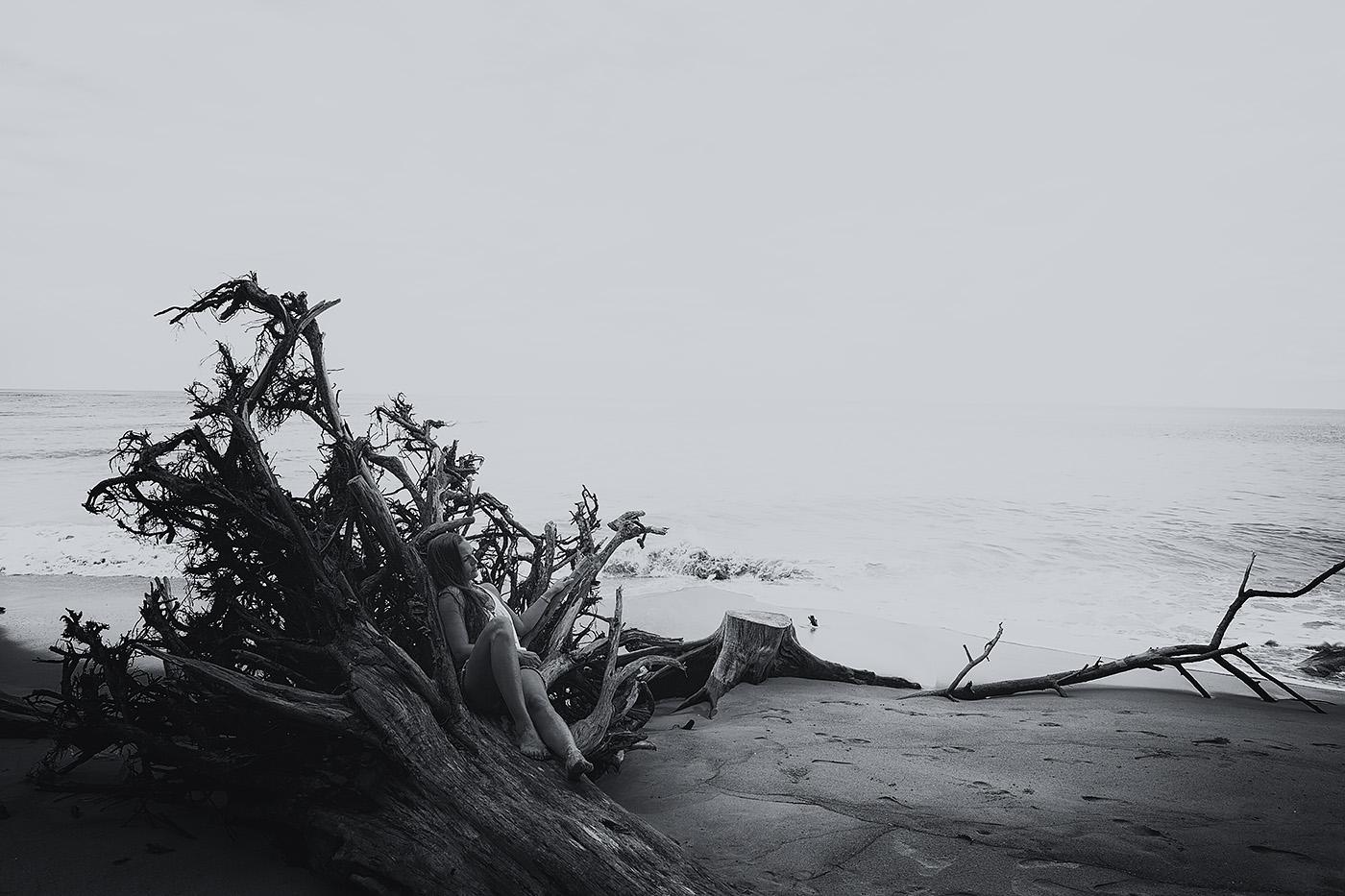 Frau liegt auf Baum an Strand in Thailand