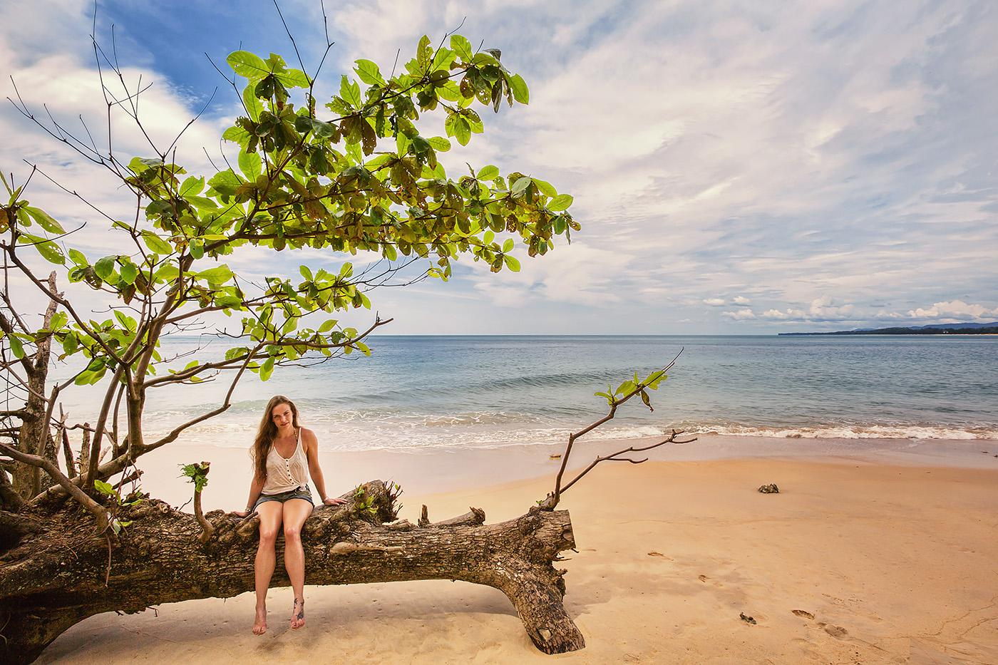 Frau sitzt auf Baum an Strand in Thailand