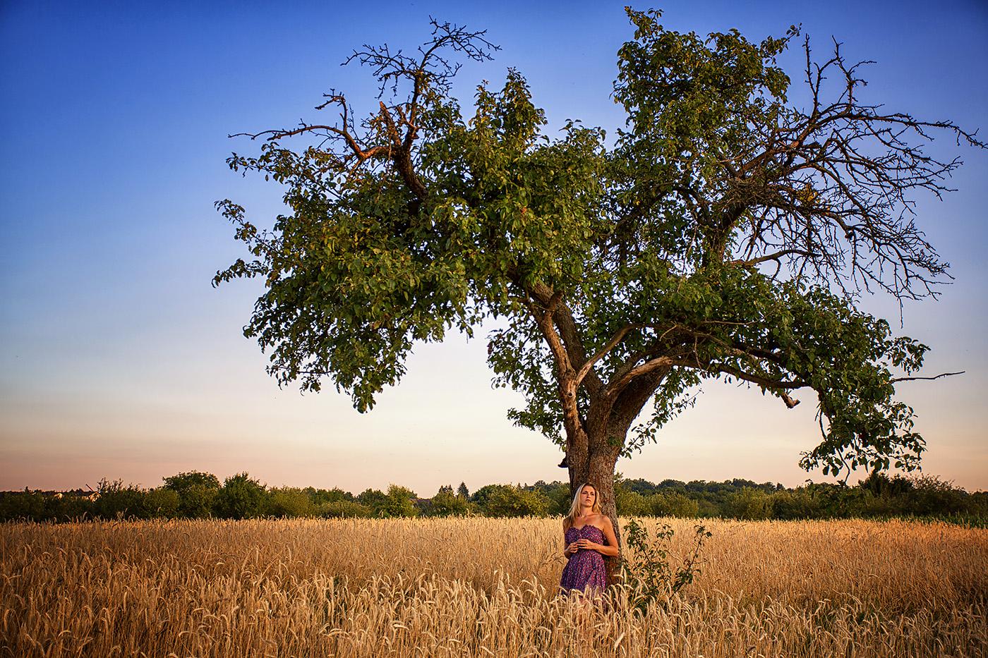 Frau in Sommerkleid an Baum im Feld