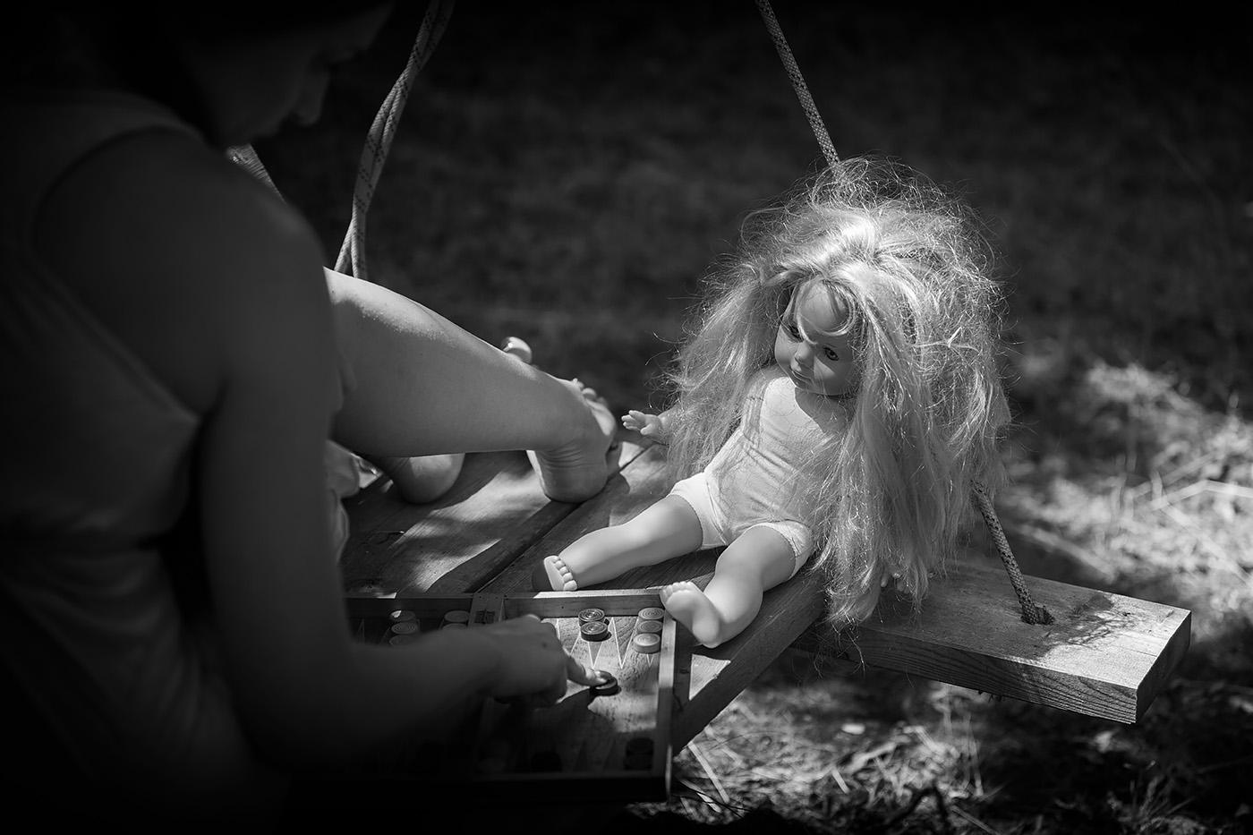 Frau spielt mit Puppe Backgammon sw