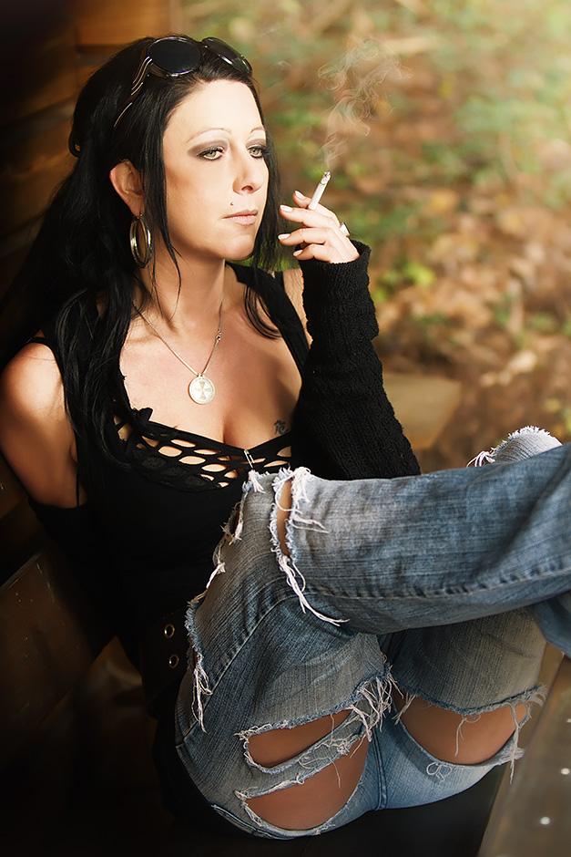 Frau in zerrissenen Jeans - rauchend