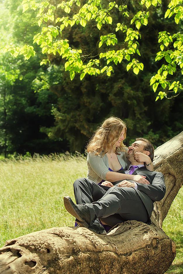 Brautpaar sitzt auf einem Baumstamm im Park Schoenbusch