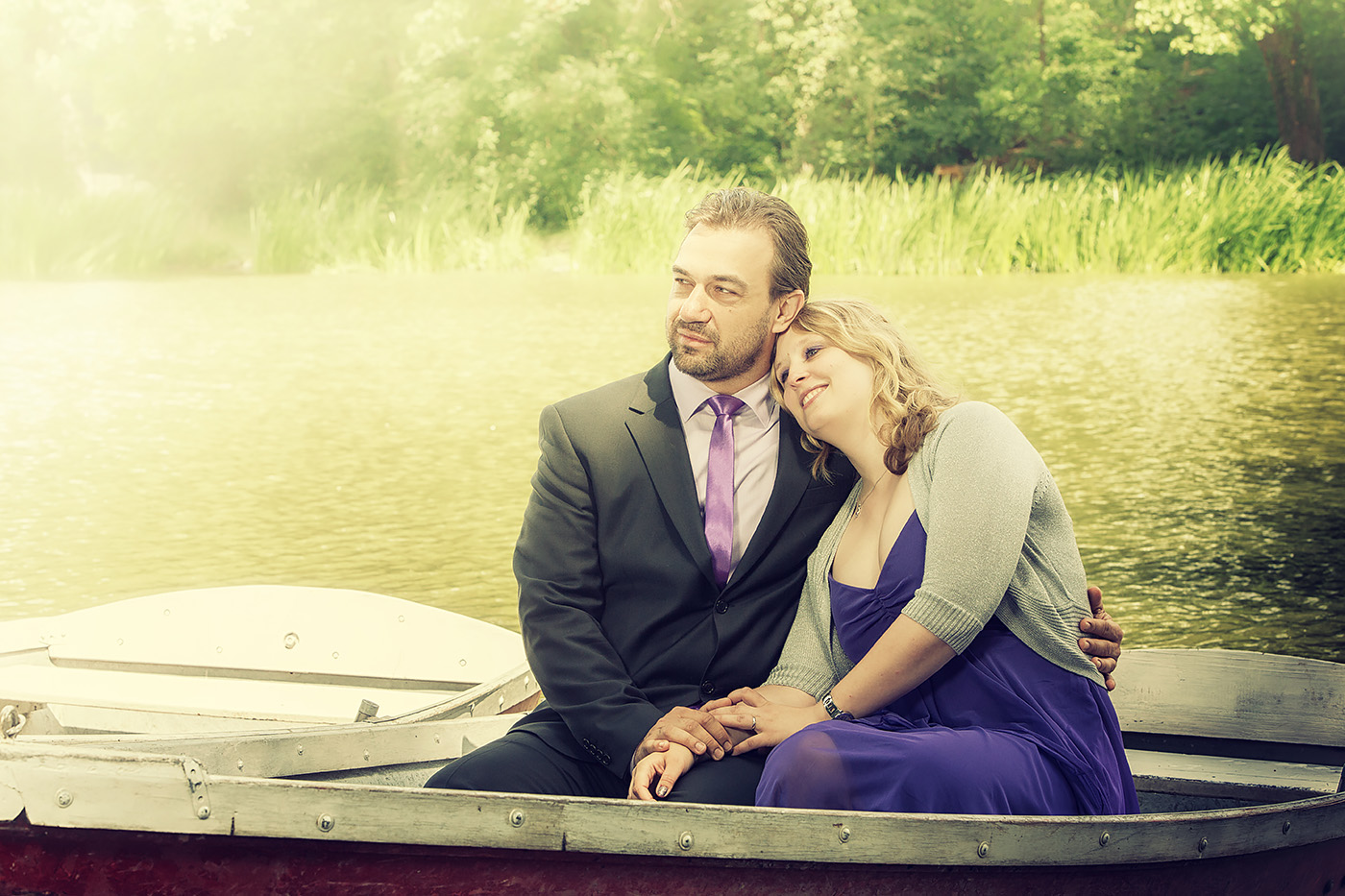 Brautpaar sitzt in einem kleinen Boot im Park Schoenbusch