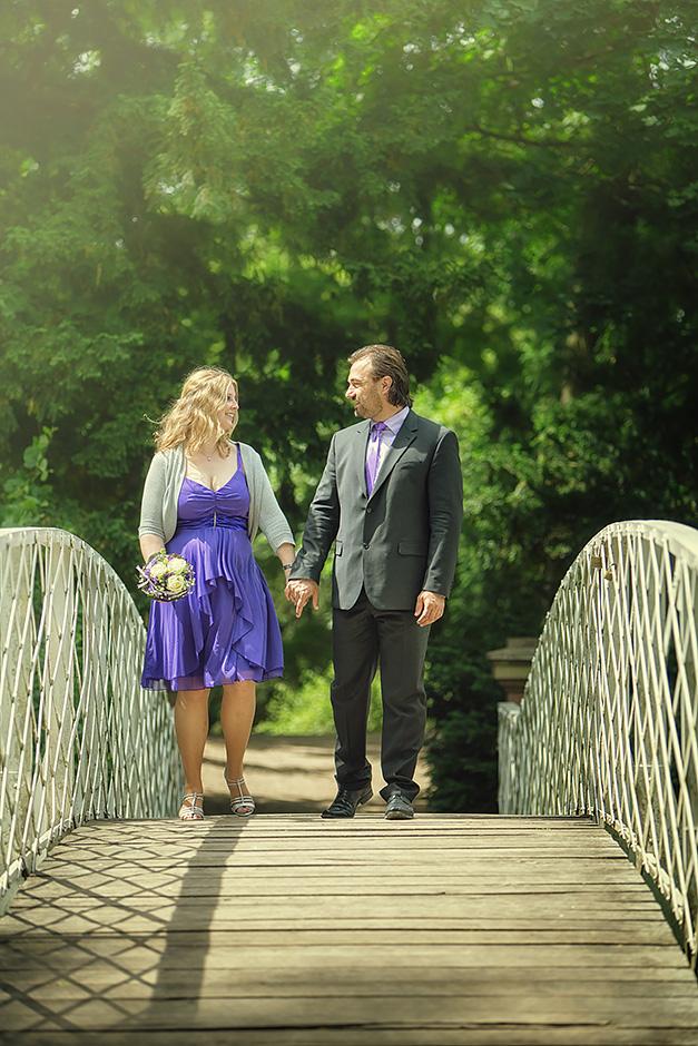 Brautpaar laeuft ueber eine Bruecke im Park Schoenbusch