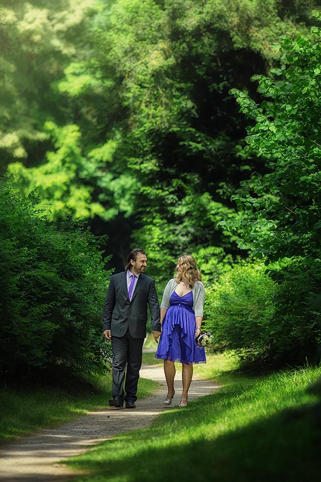 Brautpaar laeuft zwischen Baeumen im Park Schoenbusch