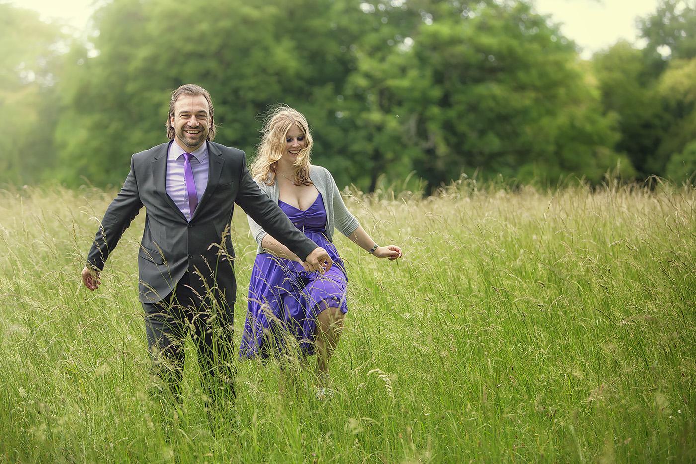 Brautpaar rennt ueber eine Wiese im Park Schoenbusch