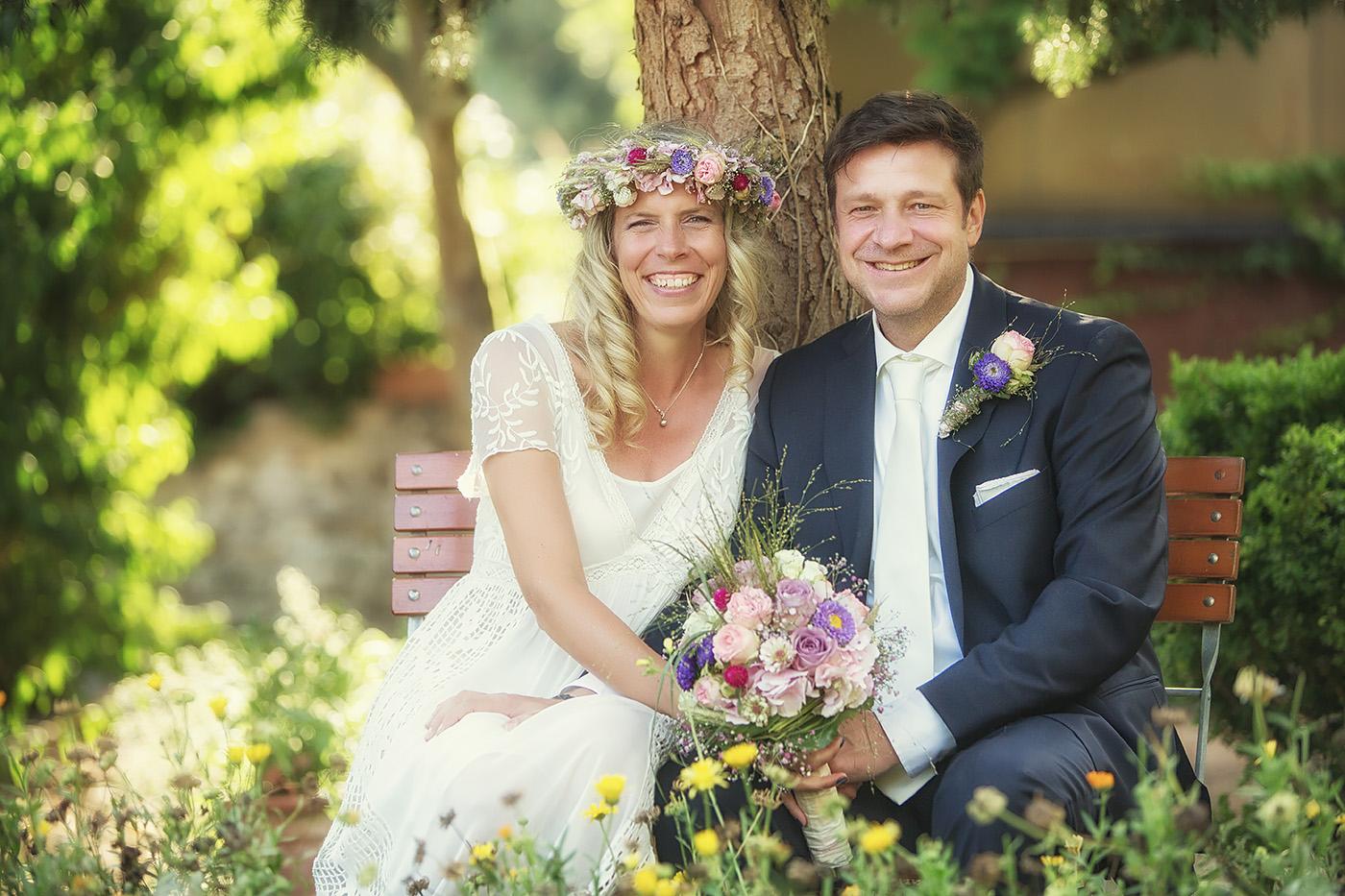Brautpaar auf einer Bank in einem Blumengarten sitzend