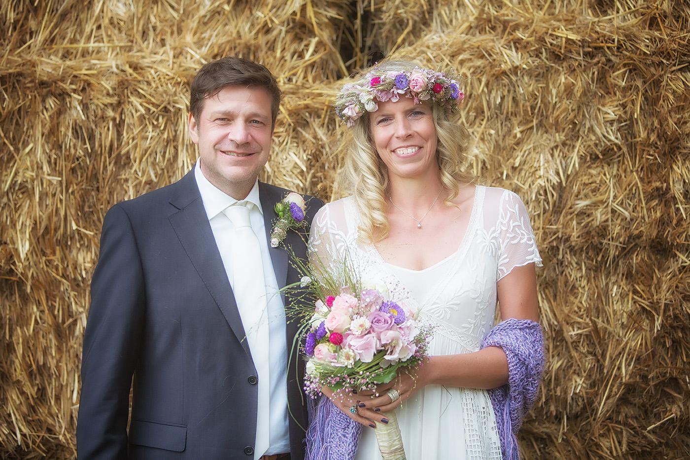 Brautpaar im Feld vor einem Heulager stehend