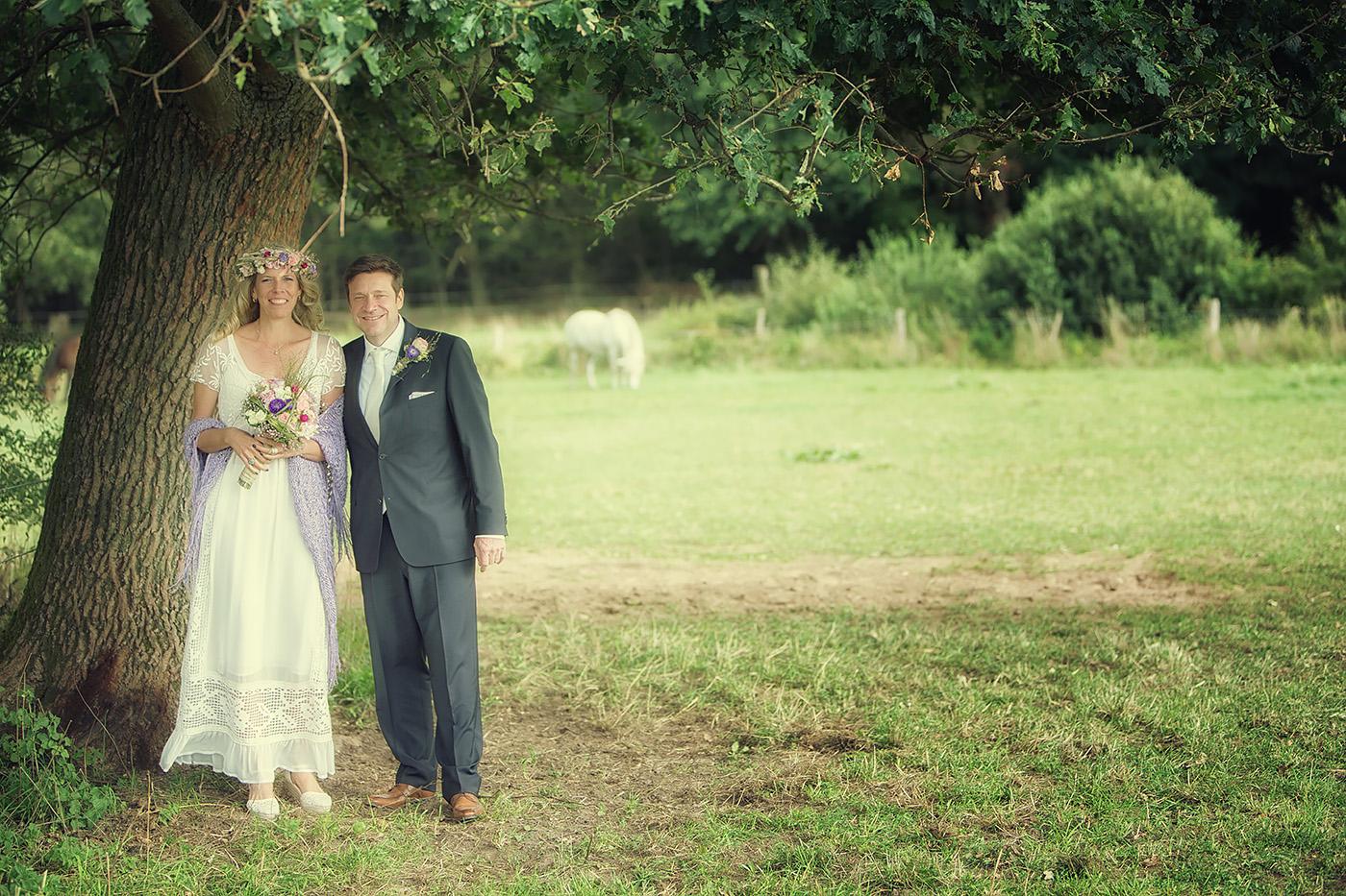Brautpaar im Feld unter einem Baum stehend
