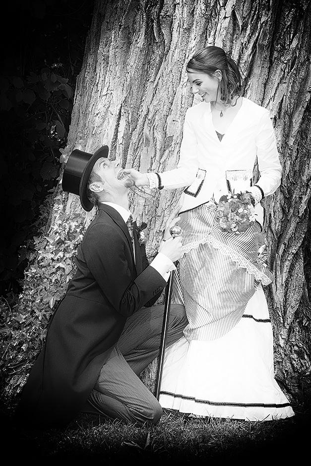 Brautpaar im vintagelook mit Frack und Zylinder, der Mann kniet vor der Braut