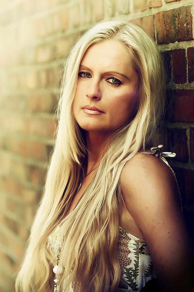 Portrait einer blonden Frauan Backsteinmauer