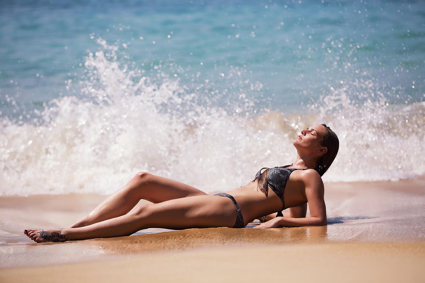 Eine Frau mit Bikini bekleidet liegt am Strand von Gran Canaria