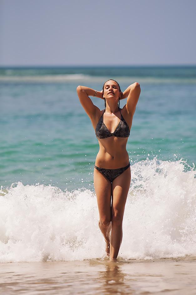 Eine Frau mit Bikini bekleidet kommt aus dem Wasser auf Gran Canaria