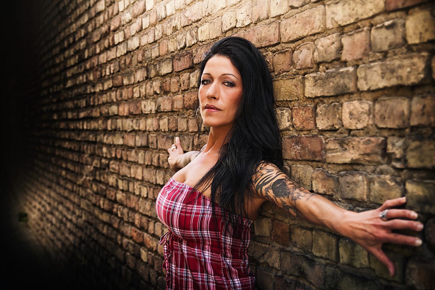 Taetowierte Frau an Backsteinmauer