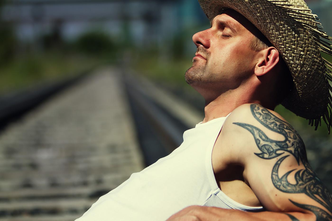 Taetowierter Mann mit Strohhut im Feinripp